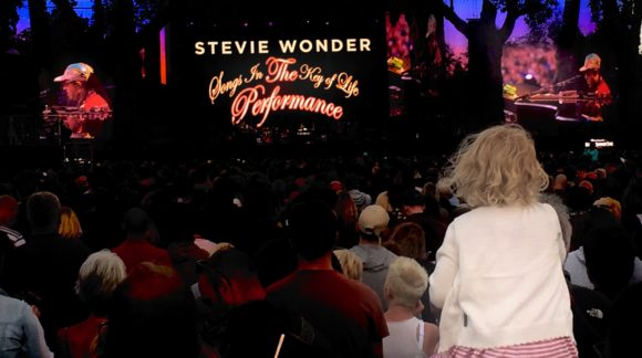 young girl on parents shoulders watching Stevie Wonder gig