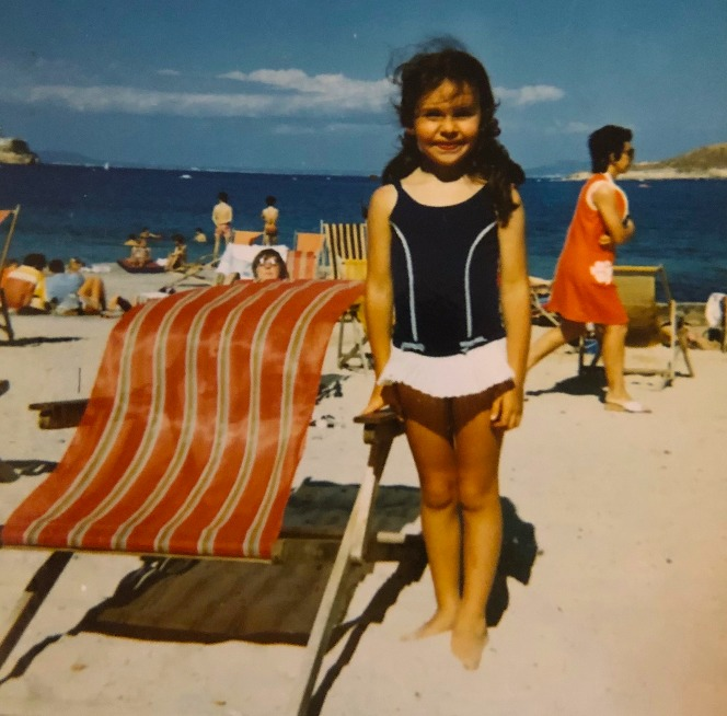 Young Julie Graham on the beach in her costume and posing next to a deckchair