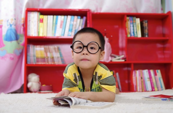 cute little Asian Boy with glasses on a rug reading a book - Maggie & Rose Life