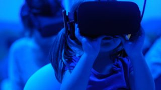 Small girl holding a VR headset to her face in a blue room